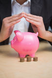 Close up of hands over piggy bank Stock Photos