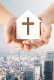 Close up of hands and paper house with cross Royalty Free Stock Images