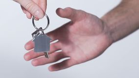 Close-up of hands passing and taking key from house, real estate rental service