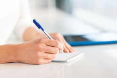 Close up of hands with pen writing to notepad Royalty Free Stock Photo