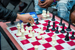 Close up of hands of people playing quick chess on the street with timer Royalty Free Stock Photo