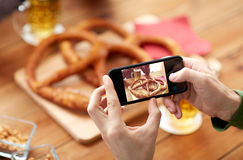 Close up of hands picturing pretzel by smartphone. People, food, and technology concept - close up of hands with smartphone picturing beer and pretzel at bar or Royalty Free Stock Photos