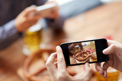 Close up of hands picturing pretzel by smartphone. People, food, and technology concept - close up of hands with smartphone picturing beer and pretzel at bar or Royalty Free Stock Photography