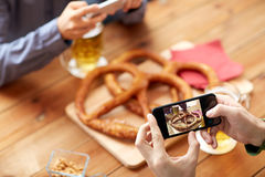 Close up of hands picturing pretzel by smartphone. People, food, and technology concept - close up of hands with smartphone picturing beer and pretzel at bar or Stock Photography