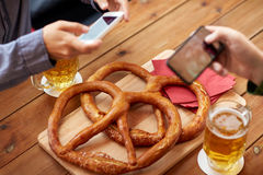 Close up of hands picturing pretzel by smartphone. People, food, and technology concept - close up of hands with smartphone picturing beer and pretzel at bar or Stock Image