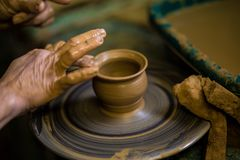 Close-up hands of potter in apron making vase from clay, selective focus. Making it together stock photo