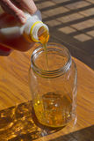 Close Up of Hands Pouring Thick Honey Into a Glass Jar Stock Images