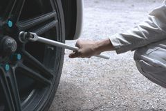Close up hands of professional mechanic in white uniform holding wrench ready to changing tire of car at garage. Close up hands of professional mechanic in Stock Image