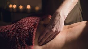 Close-up hands Professional premium massage in a dark atmospheric cabinet. Young man doing massage to a female client in