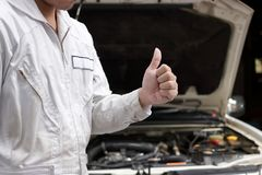 Close up hands of professional young mechanic man showing thumb up as sign of success with car in open hood at the garage backgrou Stock Photo
