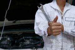 Close up hands of professional young mechanic man showing thumb up as sign of success with car in open hood at the garage backgrou Stock Photography