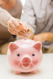 Close up of hands putting coin money to piggy bank Stock Photo