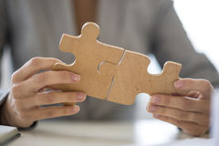 Close up on hands putting together puzzle pieces. Close up on unidentifiable business person with hands putting together two puzzle pieces stock photos