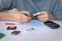 Close up of hands repairing  a mobile phone Stock Images