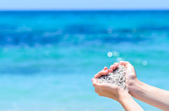 Close-up hands with sand in shape of heart against tropical turquoise sea Royalty Free Stock Image