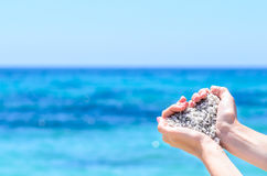 Close-up hands with sand in shape of heart against tropical turquoise sea Stock Image