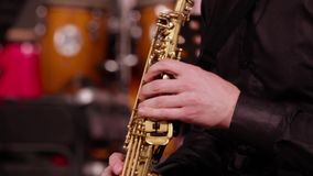 A man in a black shirt plays jazz music. Close-up of the hands of a saxophonist on a soprano saxophone.