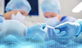 Close up of hands with scalpel at operation. Surgery, medicine and people concept - close up of surgeons hands with scalpel at operation in operating room at Royalty Free Stock Image