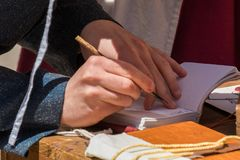 Scribe practicing traditional illumination. Close up of hands of scribe practicing traditional illumination writing calligraphy with feather quill and ink Stock Photos