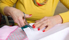 Close-up of the hands of a seamstress with scissors Stock Photo