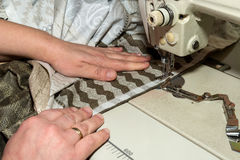 Close up hands of seamstress working on sewing machine Royalty Free Stock Photo