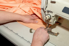 Close up hands of seamstress working on sewing machine Stock Images