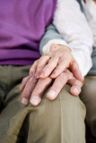 Close-up hands of senior couple resting on knee Stock Image