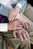 Close-up hands of senior couple resting on knees. Close-up detail of hands of senior couple touching and resting on knees royalty free stock images