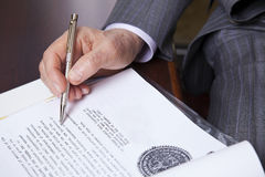 Senior About to Sign. Close up on hands of a senior (in his 80's) businessman holding a fancy pen in his right hand, about to sign a contract. Seen from a high Stock Photography