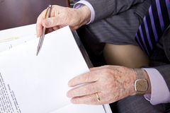 Senior About to Sign. Close up on hands of a senior (in his 80's) businessman about to sign a contract. He's holding a fancy pen in his right hand and wearing a Royalty Free Stock Photography