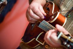 Close up hands senior man playing mandolin Royalty Free Stock Photo