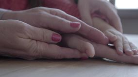 Close up of hands of senior mature woman and little girl. Grandmother spends time with granddaughter, they hold hands stock footage