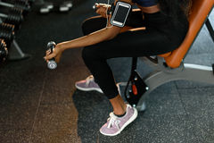 Close-up hands of sexy fitness african american woman working out with dumbbells at the gym and listens music in Royalty Free Stock Photos