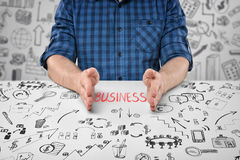 Close-up hands of sitting man with word 'business' between them and doodles around him Stock Images