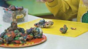 Kid`s hands molded plasticine figurines stock video footage