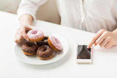 Close up of hands with smart phone and donuts Stock Photos