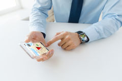 Close up of hands with smart phone and watch. Business, technology, navigation and people concept - close up of male hand holding and showing transparent smart stock photos