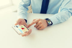 Close up of hands with smart phone and watch. Business, technology, navigation and people concept - close up of male hand holding and showing transparent smart stock image