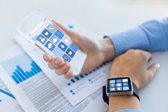 Close up of hands with smart phone and watch icons Royalty Free Stock Photo