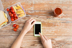 Close up of hands with smartphone food on table Royalty Free Stock Photos