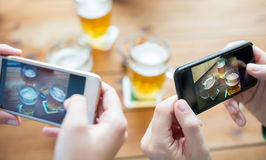 Close up of hands with smartphone picturing beer. People and technology concept - close up of hands with smartphone picturing beer at bar Royalty Free Stock Image