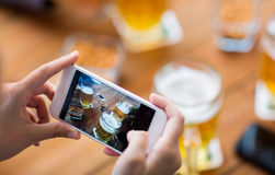 Close up of hands with smartphone picturing beer. People and technology concept - close up of hands with smartphone picturing beer at bar Royalty Free Stock Images