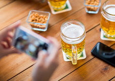 Close up of hands with smartphone picturing beer. People and technology concept - close up of hands with smartphone picturing beer at bar Stock Photo