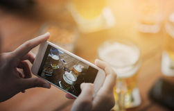 Close up of hands with smartphone picturing beer. People and technology concept - close up of hands with smartphone picturing beer at bar Royalty Free Stock Photos