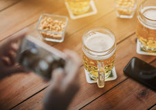 Close up of hands with smartphone picturing beer. People and technology concept - close up of hands with smartphone picturing beer at bar Royalty Free Stock Photography