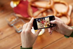 Close up of hands with smartphone picturing beer. People and technology concept - close up of hands with smartphone picturing beer and pretzel at bar or pub Royalty Free Stock Photo