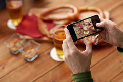 Close up of hands with smartphone picturing beer. People and technology concept - close up of hands with smartphone picturing beer and pretzel at bar or pub Stock Photography