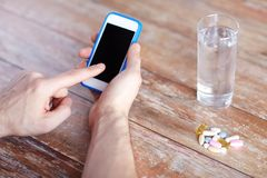 Close up of hands with smartphone, pills and water Royalty Free Stock Photography