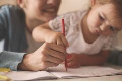 Smiling mother and little girl writing together stock images