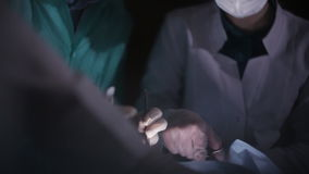 Close up hands surgical team assisting surgeon operating on patient in hospital theater stock video